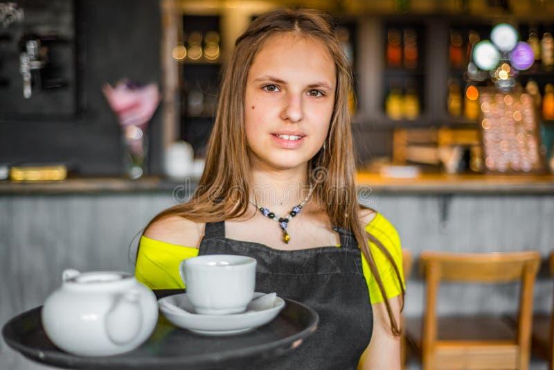 在咖啡馆的画象年轻女服务员身分 女孩侍者在束拿着有器物的一个盘子 图库摄影