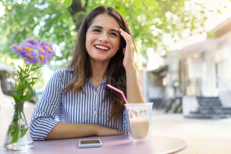 在咖啡馆的美丽的微笑的女孩饮用的咖啡户外 图库摄影
