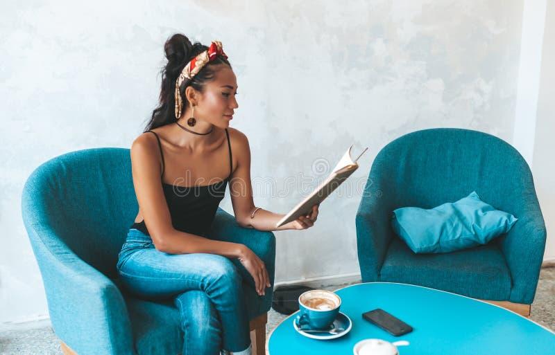 在咖啡馆的美女看书 免版税库存照片