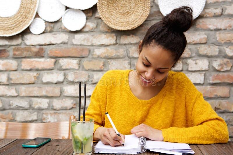 在咖啡馆的美好的年轻黑人妇女文字笔记 免版税库存照片