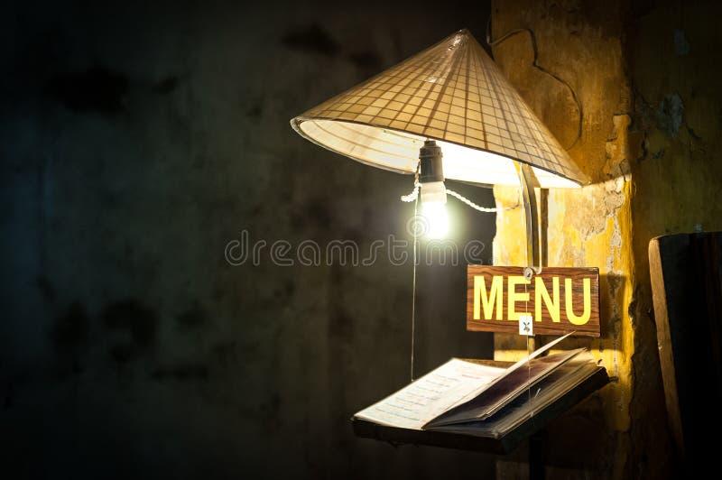 在咖啡馆的菜单在电灯泡下光在米帽子的。 库存照片