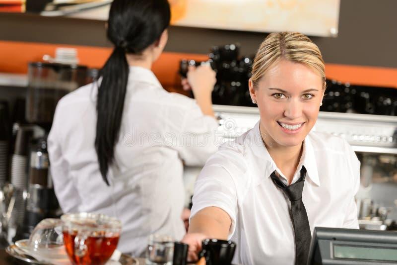 给在咖啡馆的年轻女服务员出纳员咖啡 库存照片