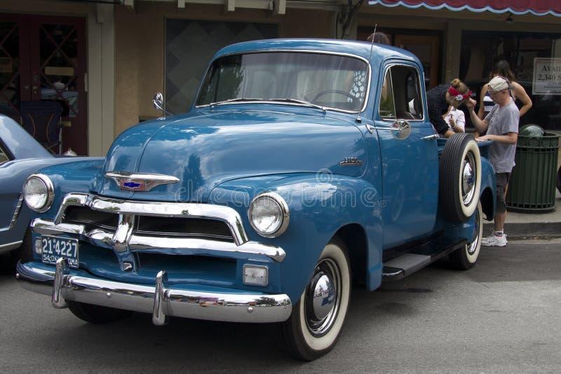 在咖啡馆附近的蓝色雪佛兰卡车 正面图 图库摄影