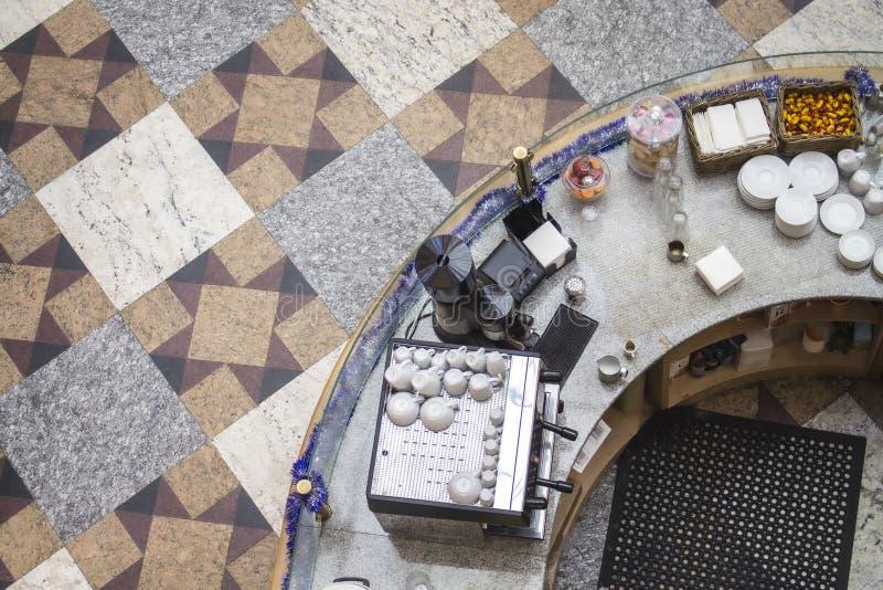 在咖啡馆顶视图的酒吧柜台 盘杯子茶碟咖啡机糖果餐巾,做的不同设备  库存照片