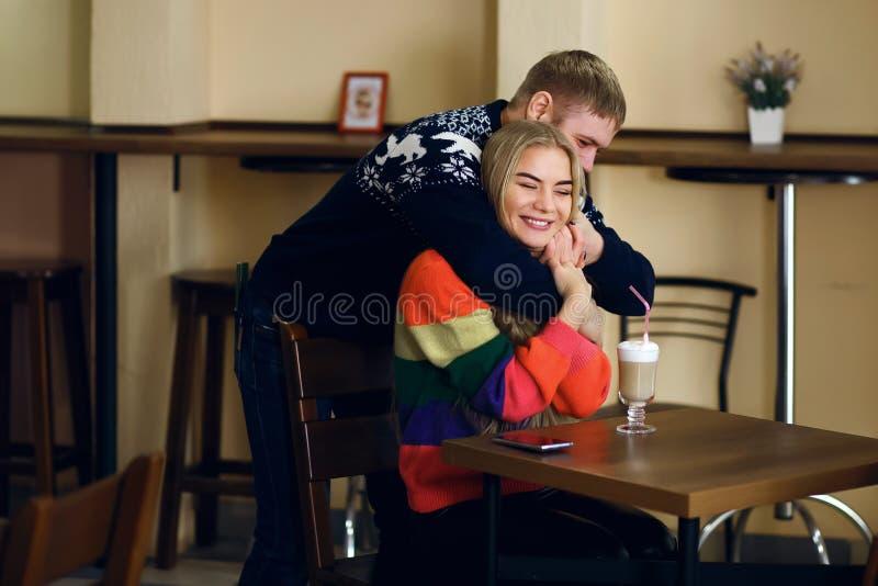在咖啡馆,一个人遇见一名妇女,人拥抱一个女孩,他们是愉快看朋友的朋友,一对年轻夫妇微笑并且享用 库存图片