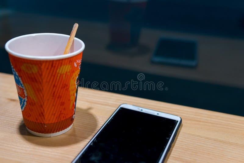 在咖啡馆,夜间,黑暗的题材的木桌 智能手机和茶,咖啡 聊天的概念,工作,写博克,在网上学会 图库摄影