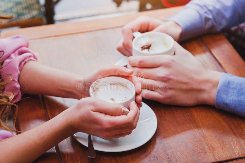 在咖啡馆,夫妇手特写镜头的人饮用的咖啡  免版税库存照片