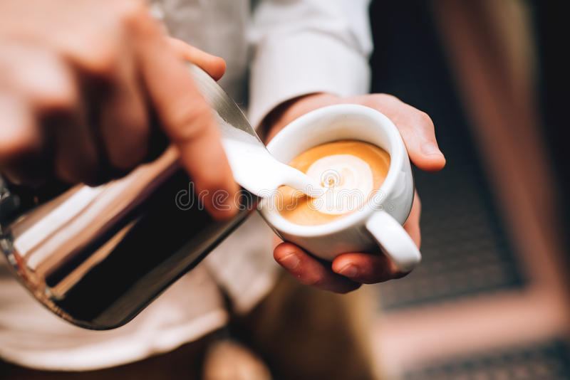 在咖啡,浓咖啡和创造一杯完善的热奶咖啡的Barista倾吐的拿铁泡沫 免版税库存图片