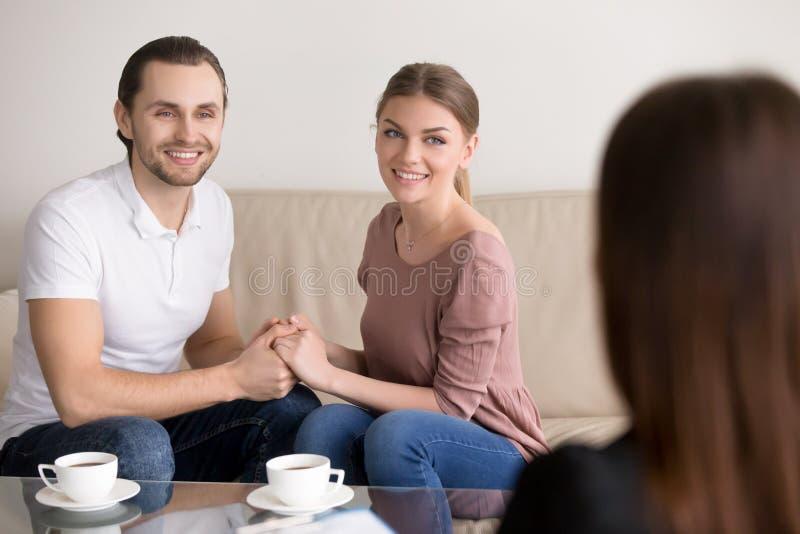 在咨询的快乐的年轻家庭夫妇 握手和 免版税库存照片