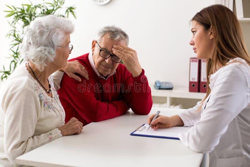 在咨询的资深夫妇与医生 库存图片