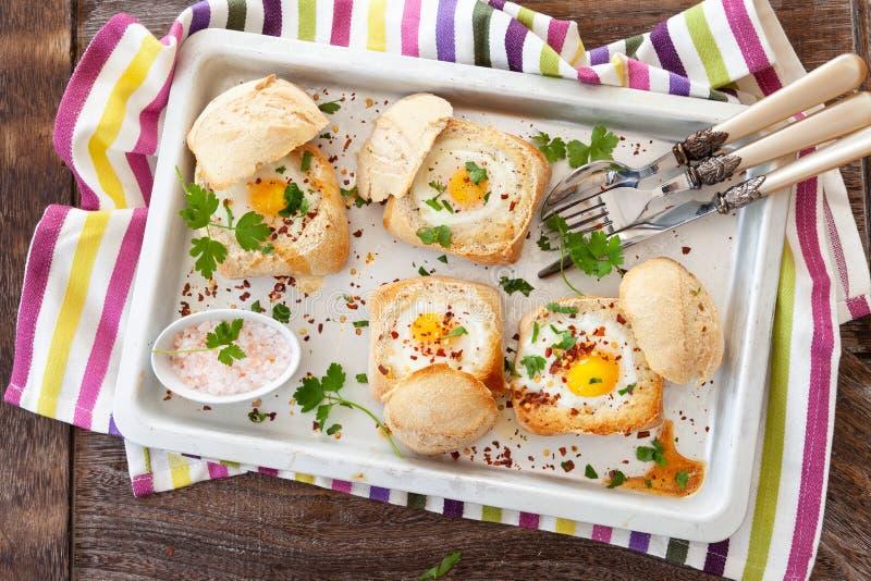 在咬嚼小圆面包的鸡蛋 免版税图库摄影
