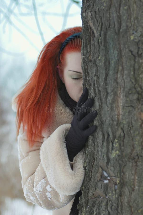 在哀伤的结构树附近的女孩 库存照片