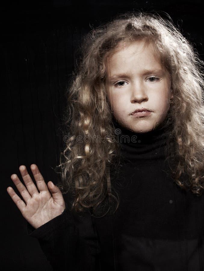 在哀伤的视窗附近的女孩 免版税库存图片