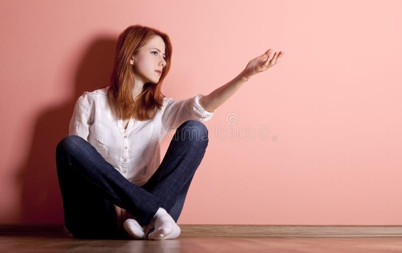 在哀伤的青少年的墙壁附近的楼层女孩 免版税库存照片