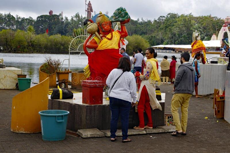 在哈奴曼上帝雕象附近的Faithul在印度寺庙和甘加Talao ??Bassin?Crater? ? 免版税图库摄影