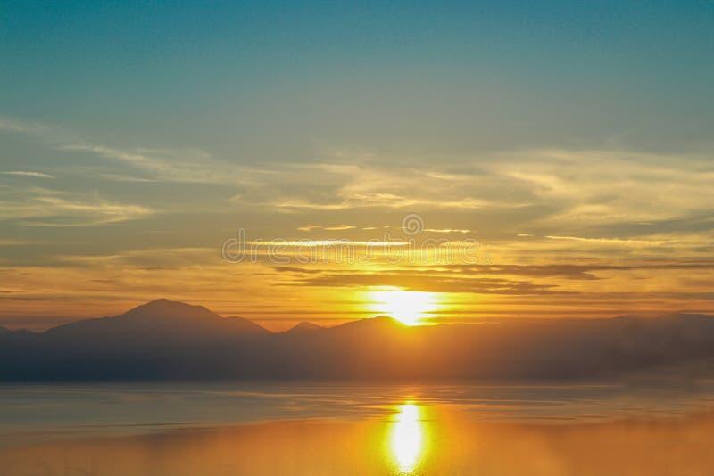 在哥林斯湾的水反映的剧烈的日落大陆的希腊朝向山往从的特尔斐 库存照片