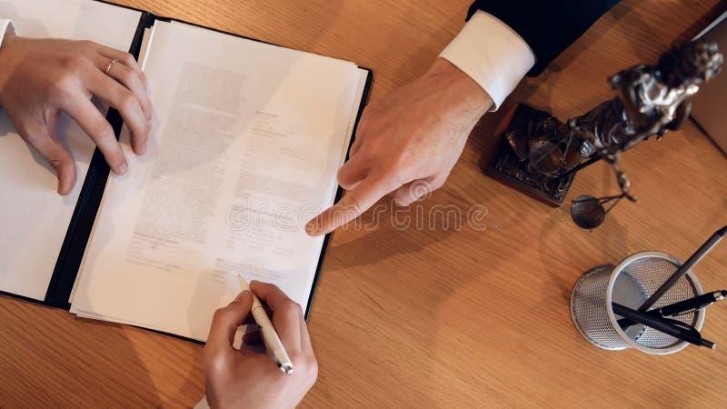 在哪里供以人员` s与手指的手点把署名放在文件上 在离婚的签署的合同 库存图片
