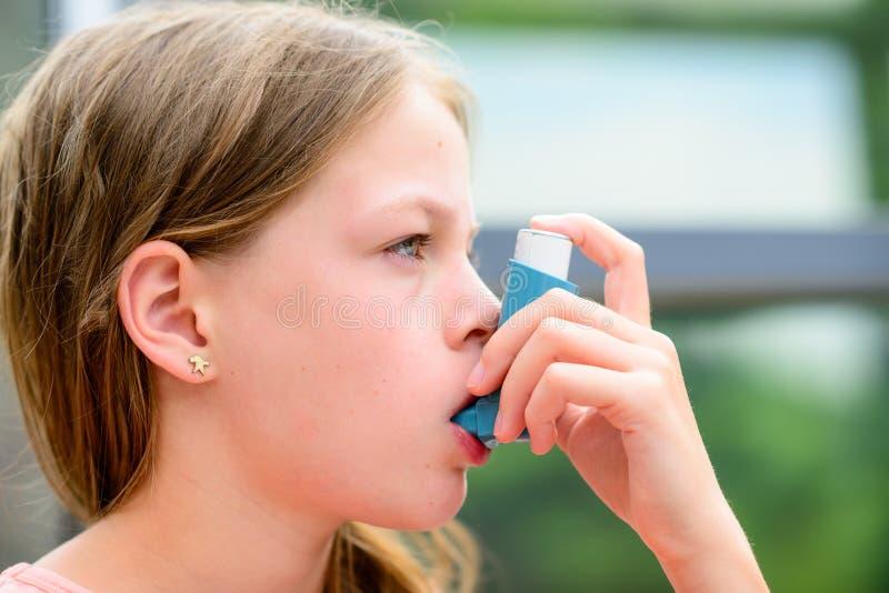 在哮喘病发作期间,女孩使用一台吸入器 图库摄影