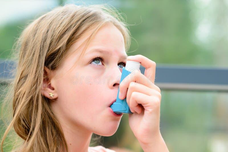 在哮喘病发作期间,女孩使用一台吸入器 库存图片