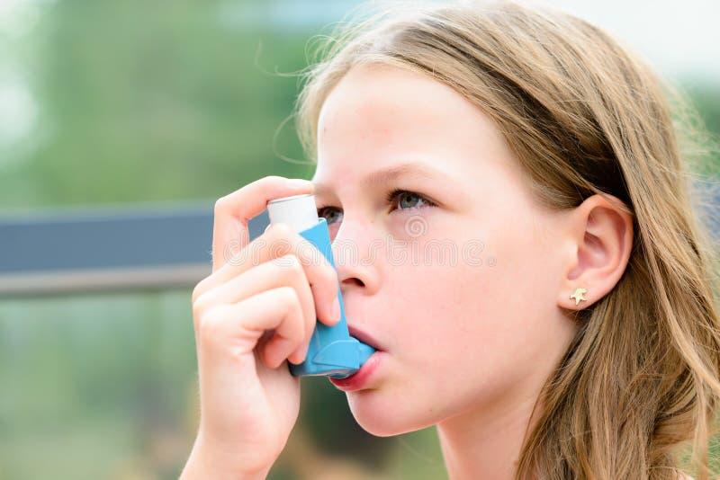 在哮喘病发作期间,女孩使用一台吸入器 免版税图库摄影