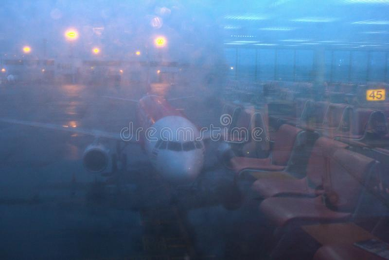 在唐Mueang机场的形成弧光的航空器通过门窗口 反射在门的镜子 库存图片