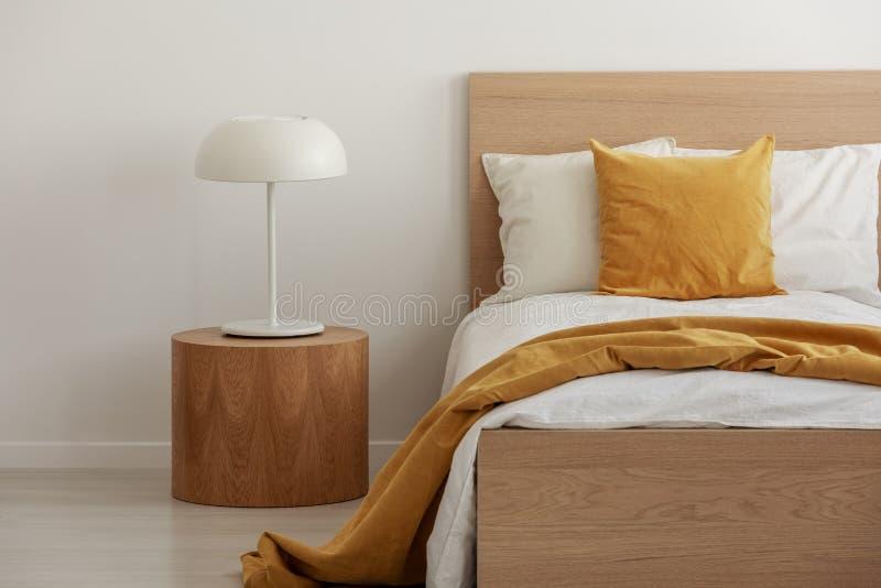 在唯一木床上的白色和黄色卧具在当代旅馆内部 免版税库存图片