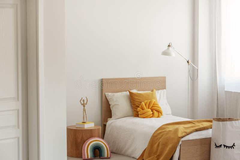 在唯一木床上的白色和黄色卧具在当代旅馆内部 免版税图库摄影