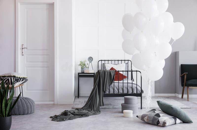 在唯一金属床旁边的白色气球与灰色卧具和白色和深红枕头在明亮的斯堪的纳维亚卧室 图库摄影