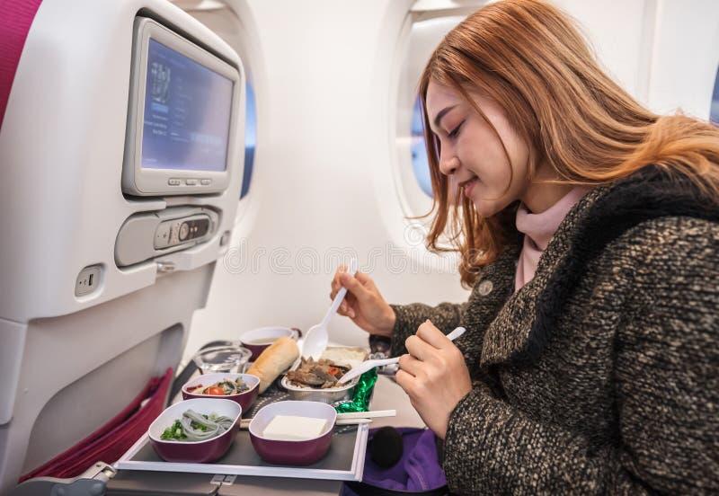 在商业飞机的妇女吃饭在飞行中计时 免版税库存图片