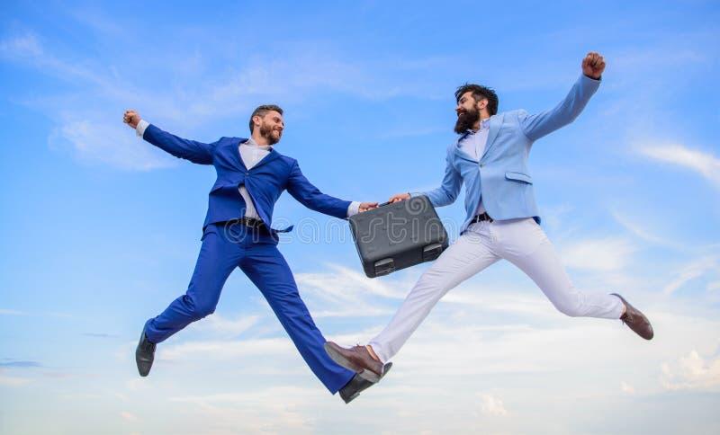 在商人之间的成功的交易 公文包移交在天堂蓝天背景中 容易的成交事务 库存照片