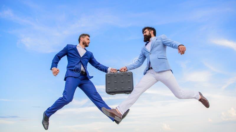 在商人之间的成功的交易 容易的成交事务 商人跳飞行空中,当举行公文包时 案件 免版税库存图片