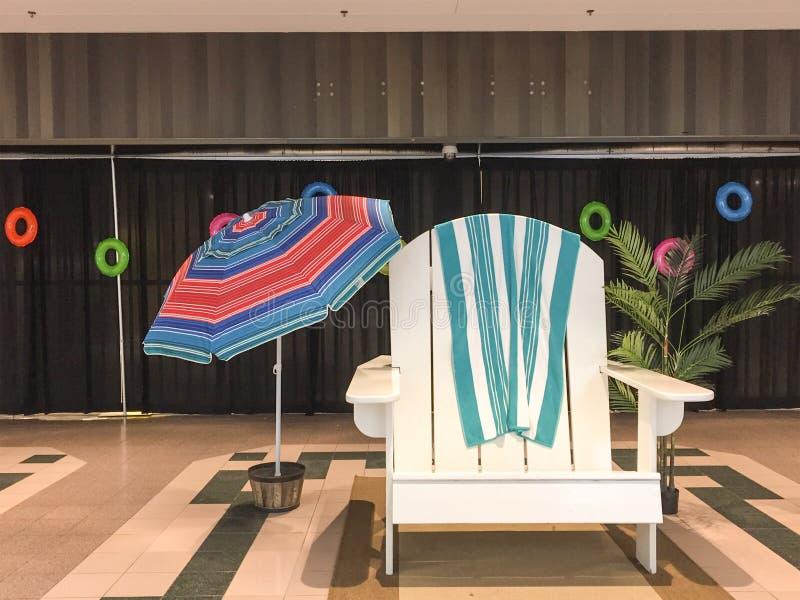 在商城的巨型夏天海滩睡椅和伞场面 免版税图库摄影