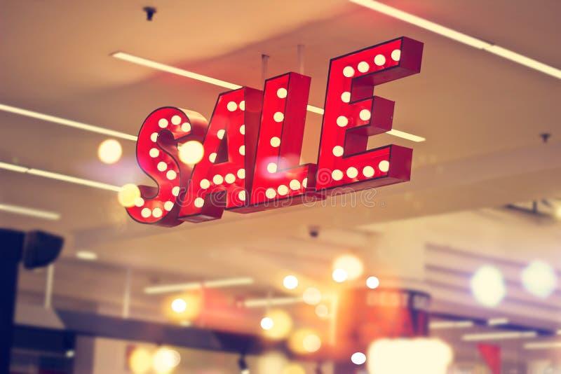 在商城背景的红色金属标志商店照明设备 免版税图库摄影