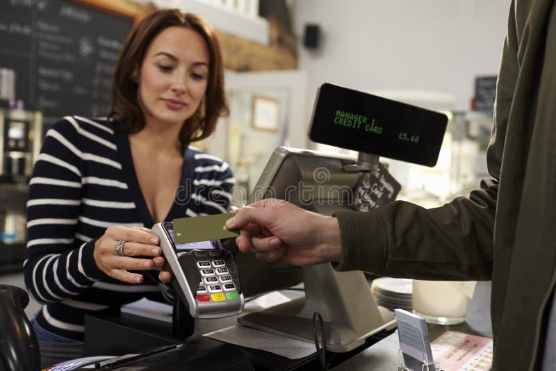 付在商店柜台的顾客不接触的卡片付款 库存照片