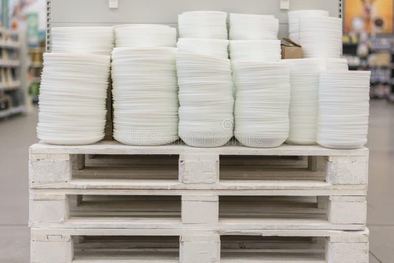 在商店白色集合烹调的架子的许多板材 在各种各样的白色板材的架子在商店 厨房瓷 图库摄影