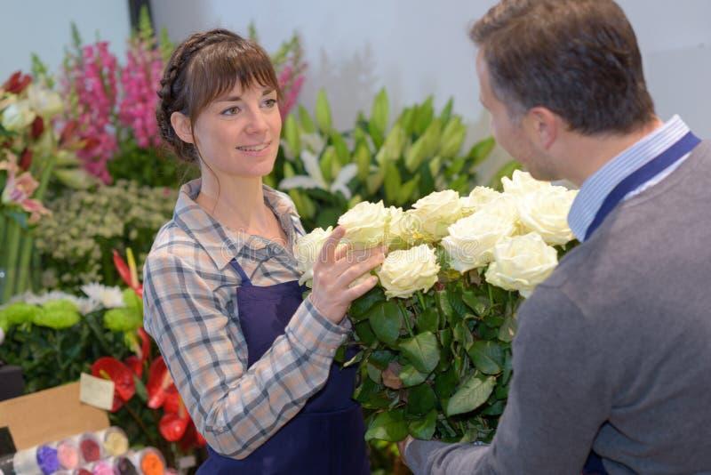 在商店的卖花人和男性顾客嗅到的花花束 免版税库存图片