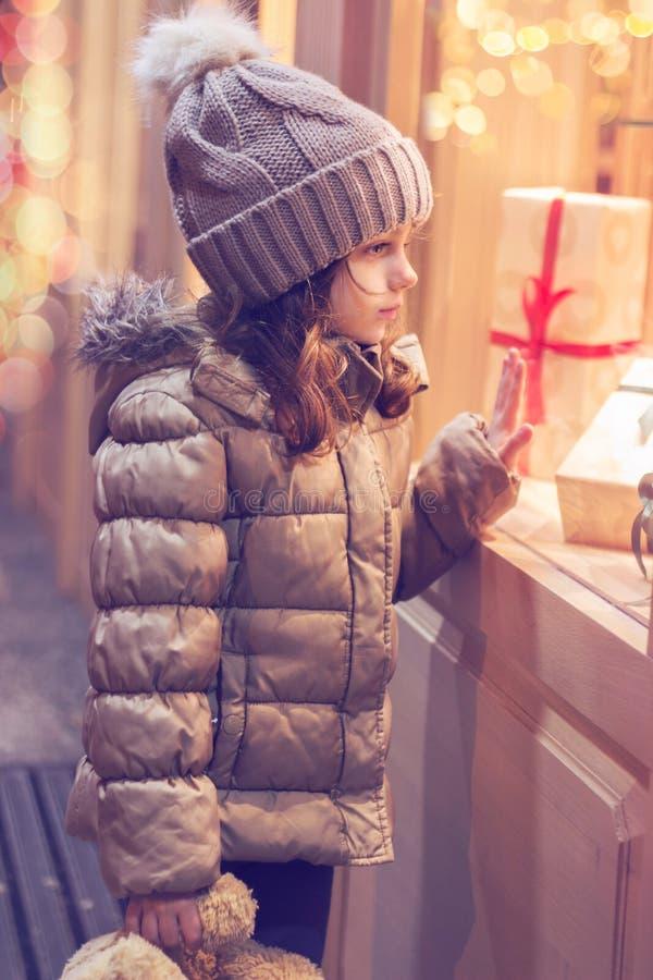 在商店的窗口的前面女孩,有很多被包裹的礼物;圣诞节背景 免版税库存照片