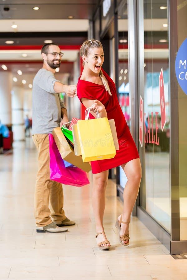 在商店窗口的夫妇在购物中心购物 免版税库存图片