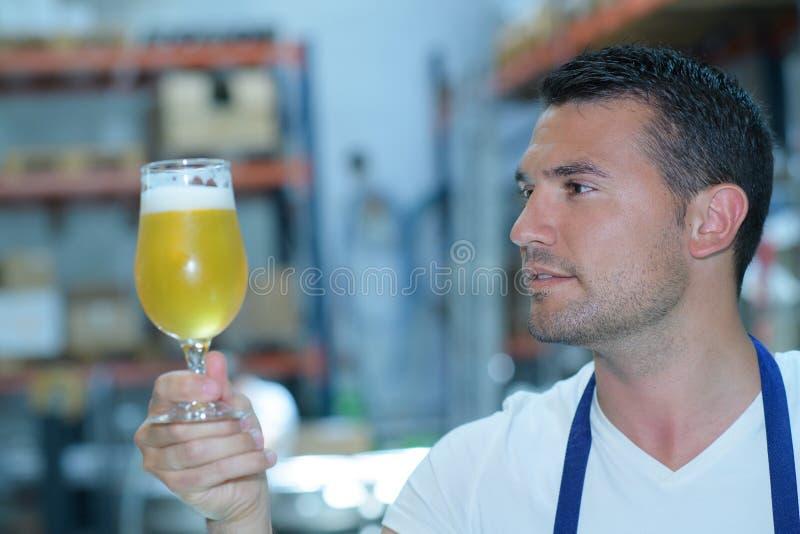 在啤酒厂的酿酒者测试的啤酒 库存照片