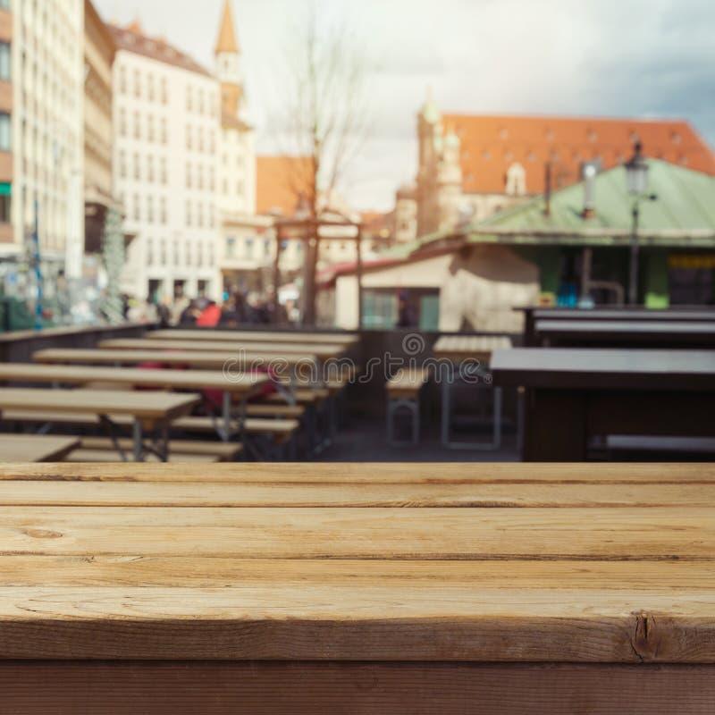 在啤酒庭院餐馆背景的空的木甲板桌产品蒙太奇显示的 Octoberfest 免版税库存图片