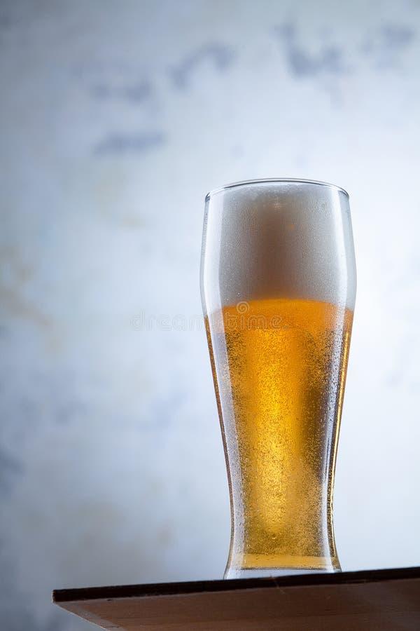 在啤酒立场冷玻璃杯的接近的看法在一个混凝土墙前面的 酒精冷的饮料 E 客栈概念 免版税库存照片