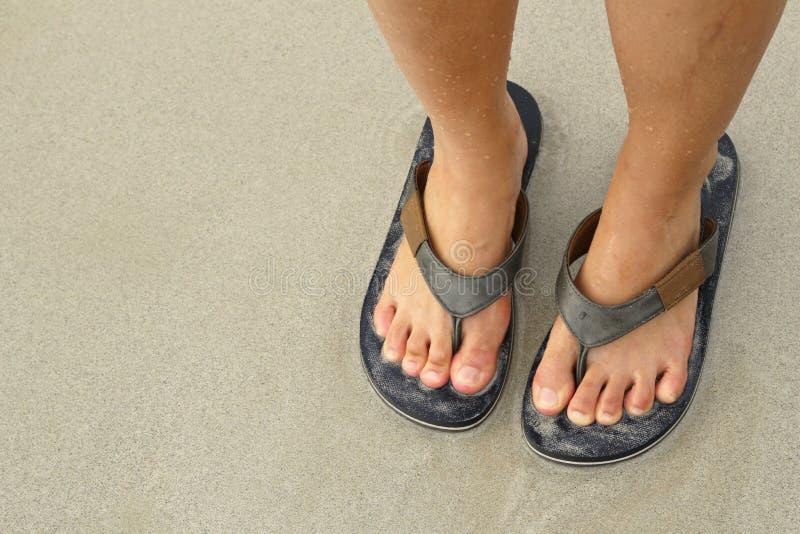 在啪嗒啪嗒的响声凉鞋的女孩腿在海靠岸 图库摄影