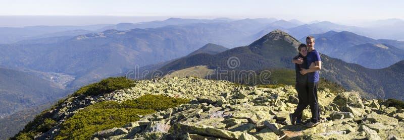 在喀尔巴阡山脉的年轻夫妇暴涨 站立在下面山顶面看的美好的风景的男人和妇女 宽Panor 免版税库存图片