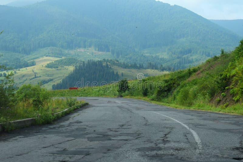 在喀尔巴阡山脉的损坏的路,在乌克兰 与坑洼的破裂的沥青沥青路 夏天风景,森林,天空 免版税库存照片