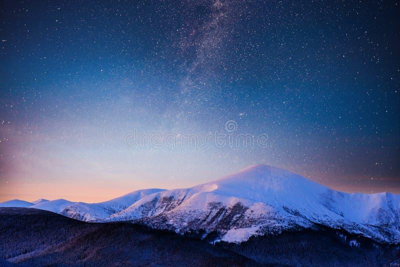 在喀尔巴阡山脉的美好的冬天风景 与星的充满活力的夜空和星云和星系 深天空 库存照片