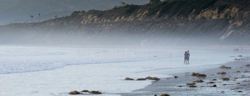 在喜怒无常的海滩的夫妇 库存照片