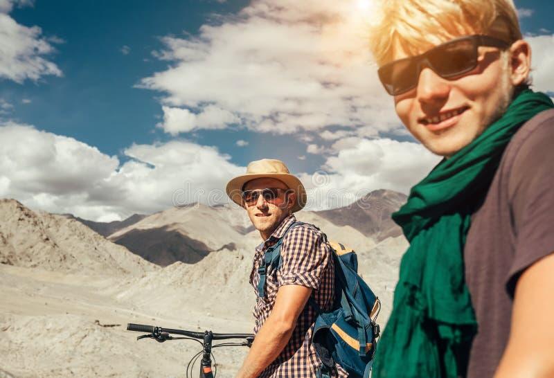 在喜马拉雅山视图的两个山骑自行车的人画象 库存图片