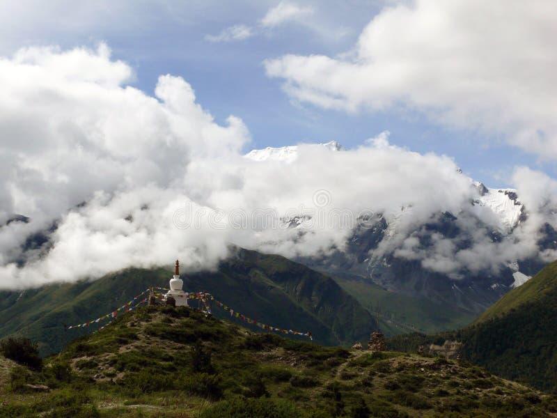 在喜马拉雅峰顶前的佛陀Stupa和季风云彩 库存图片