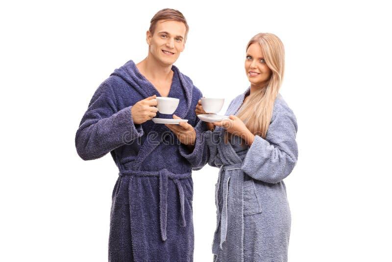 在喝咖啡的浴巾的快乐的夫妇 库存照片