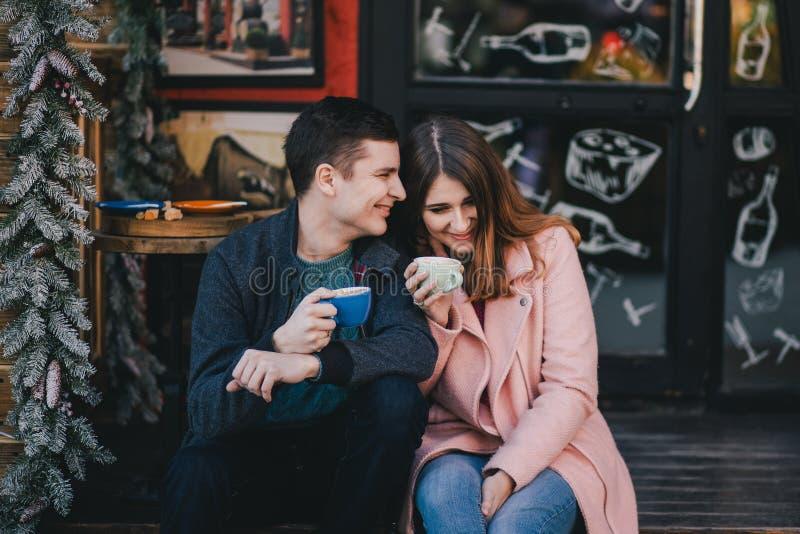 在喝在圣诞节市场上的温暖的衣裳的愉快的夫妇咖啡 免版税库存图片